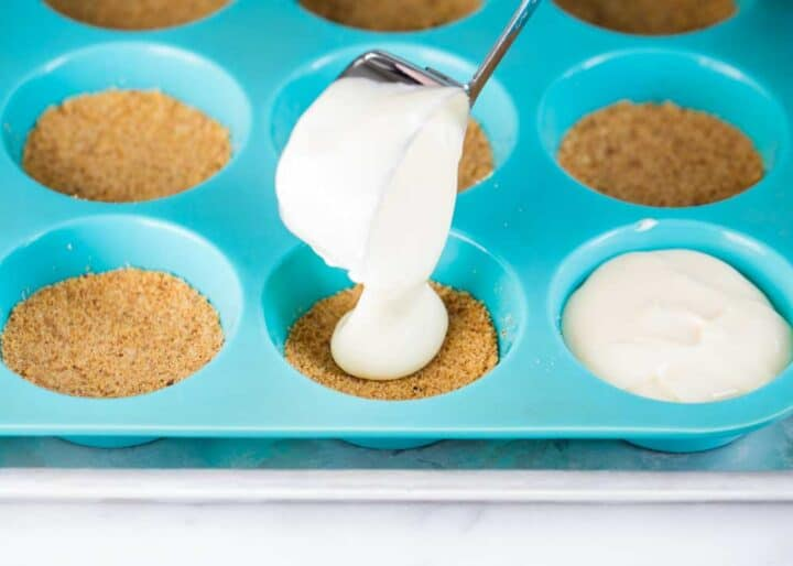 pouring cheesecake filling over graham cracker crust in muffin pan