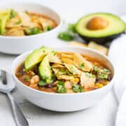 bowl of chicken tortilla soup with sliced avocado and crushed tortilla chips