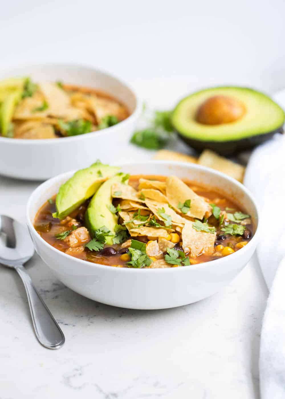 Chicken tortilla soup in white bowls with avocado