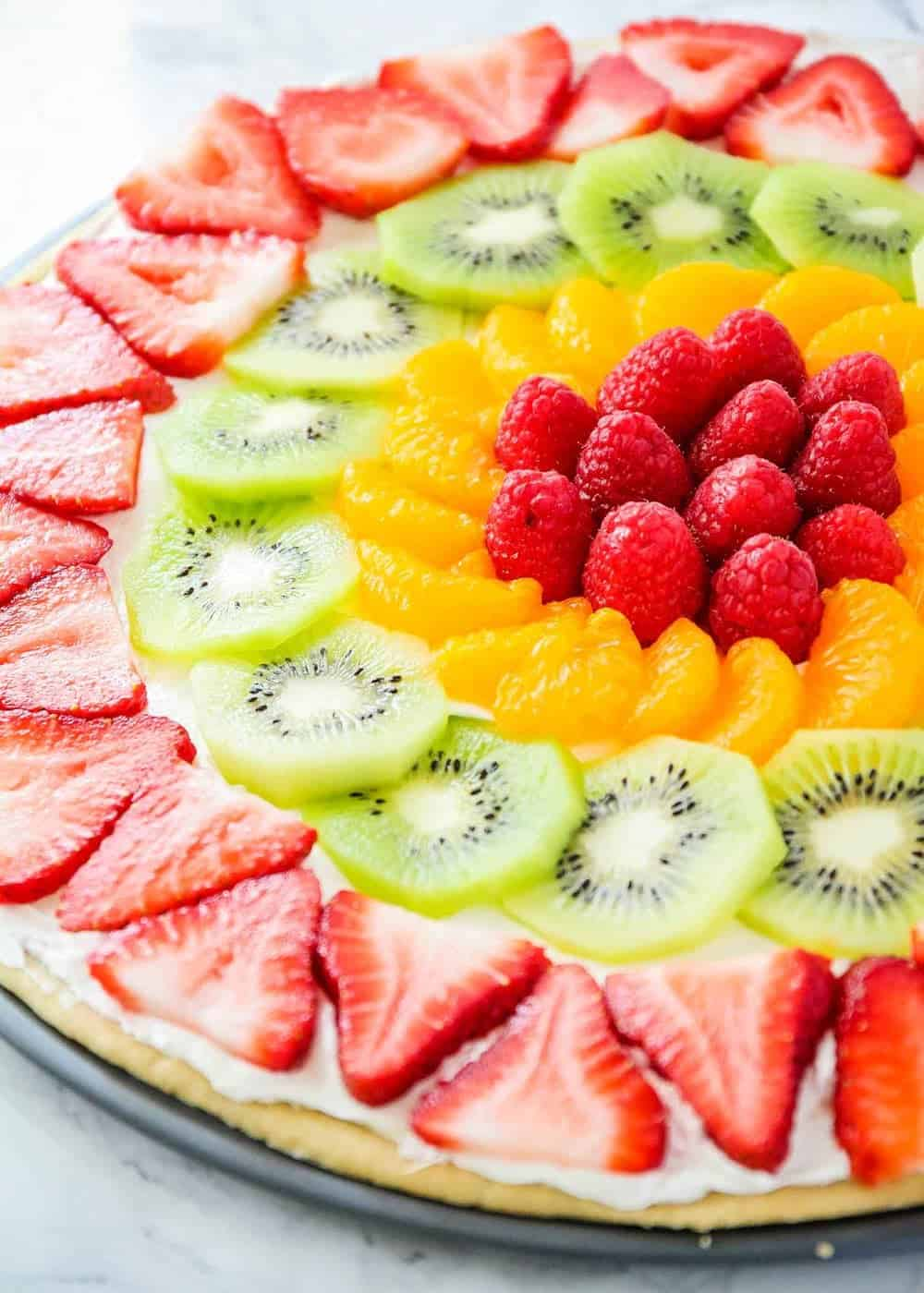sugar cookie fruit pizza with strawberries, kiwi, mandarin oranges and raspberries
