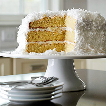 coconut cake on cake stand with slice taken out