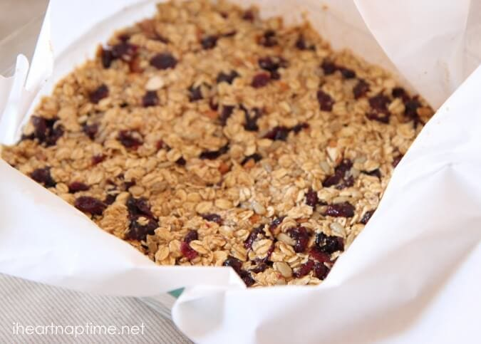 homemade granola bar mixture in baking pan with wax paper