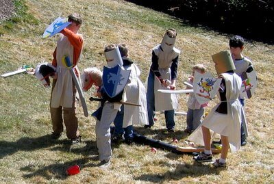 little kids dressed up as knights standing on the grass