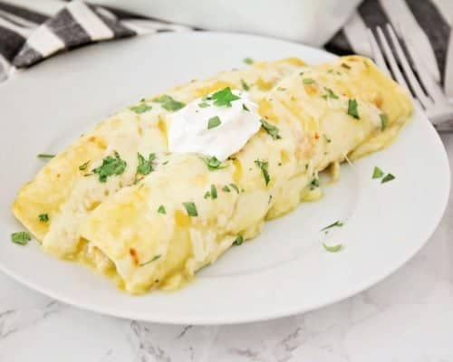 green chile chicken enchiladas on a white plate