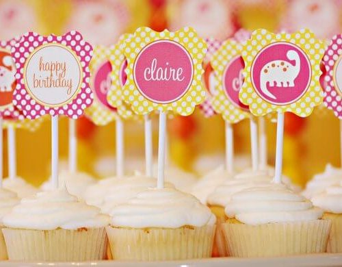 vanilla cupcakes with pink and yellow birthday cupcake toppers