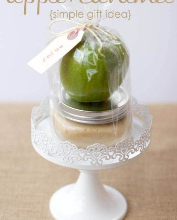 wrapped caramel apple gift sitting on cake stand
