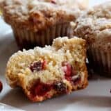 A close up of a crumb topped cranberry eggnog muffin sliced in half