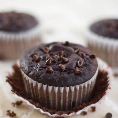 A close up of a chocolate muffin in muffin liner