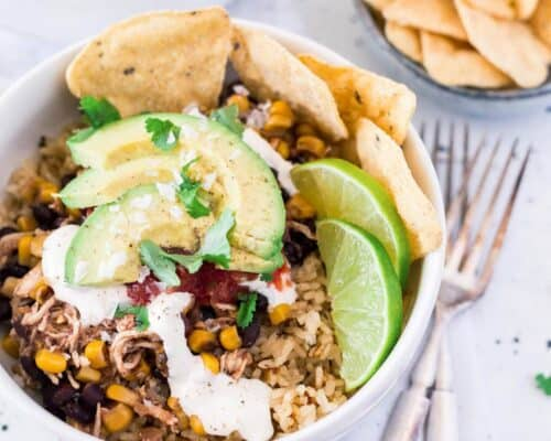 chicken taco bowl topped with sliced avocado, sour cream, cilantro, fresh limes and tortilla chips