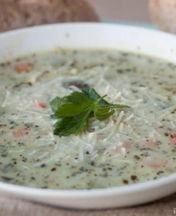 A close up of a bowl of chicken and orzo pesto soup