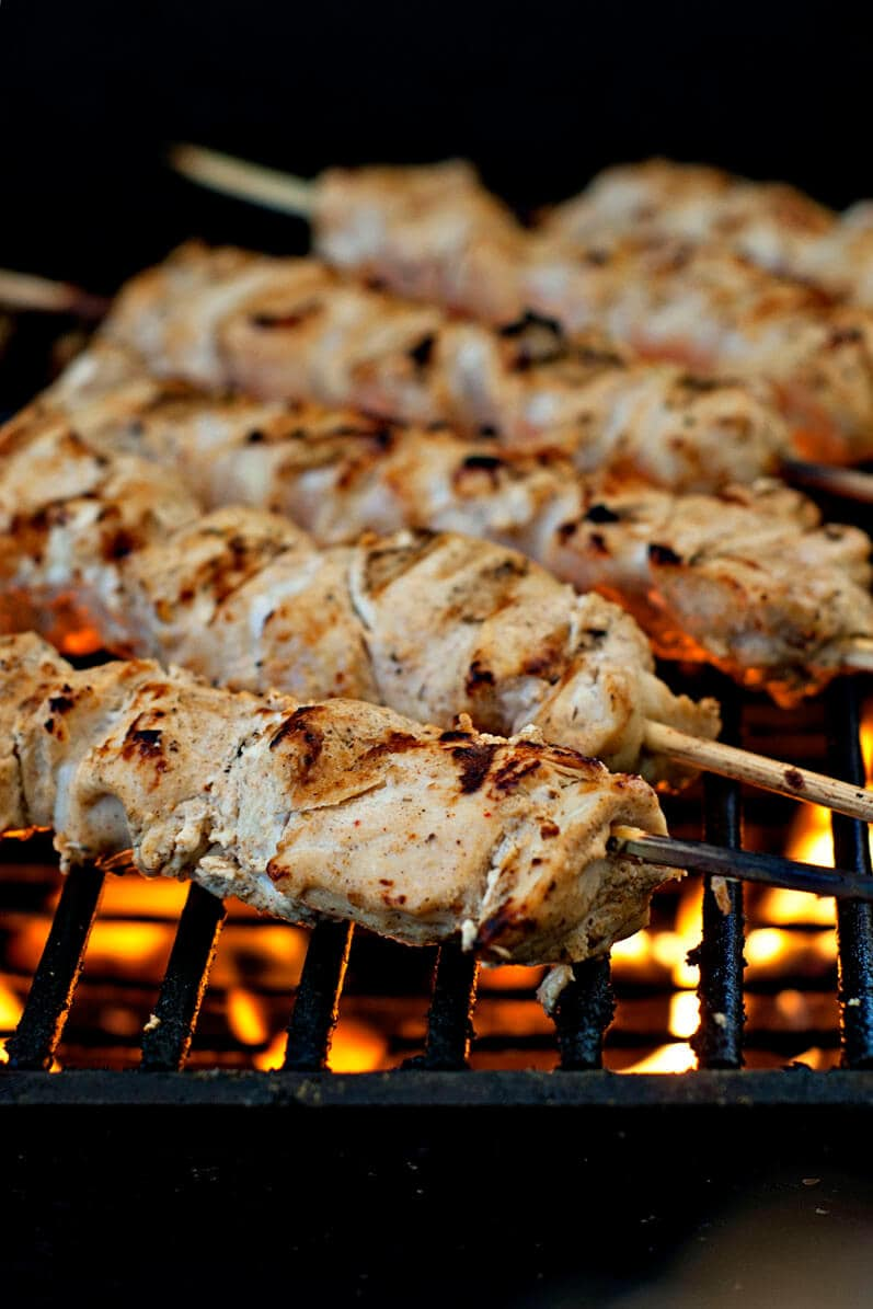 cooking chicken skewers on grill