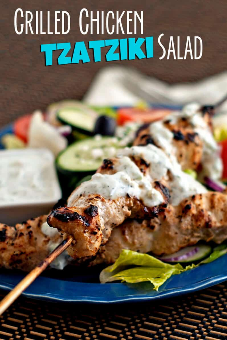 grilled chicken skewers on top of salad with tzatziki sauce