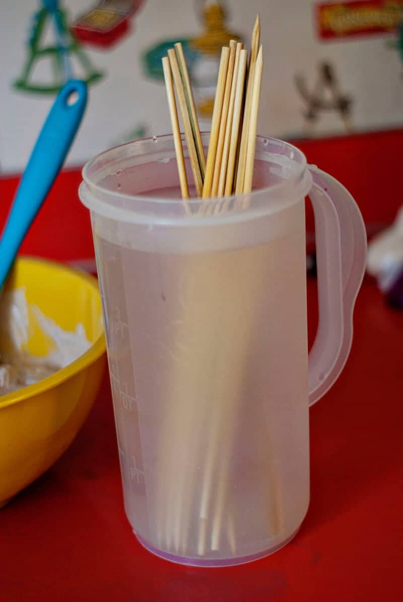 a cup with wooden skewers in it