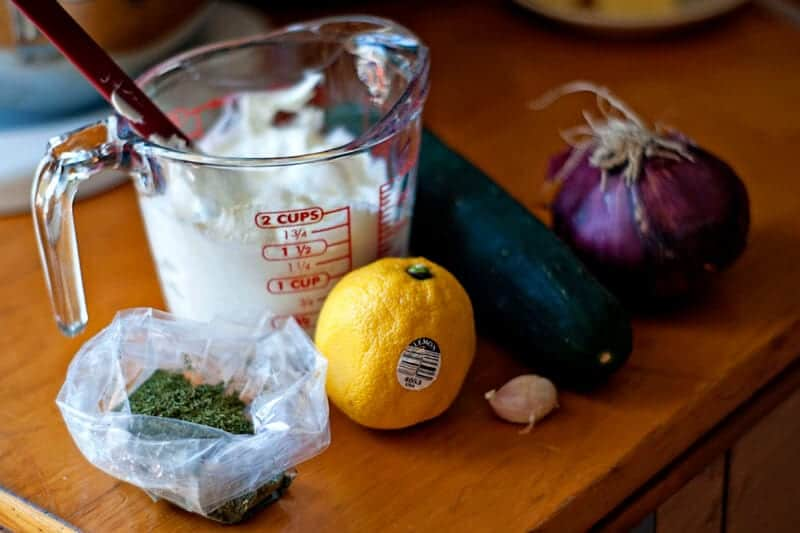 ingredients for tzatziki sauce sitting on wood counter