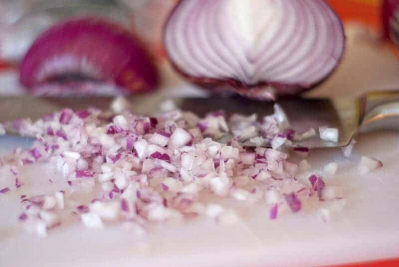 chopping a red onion with a knife