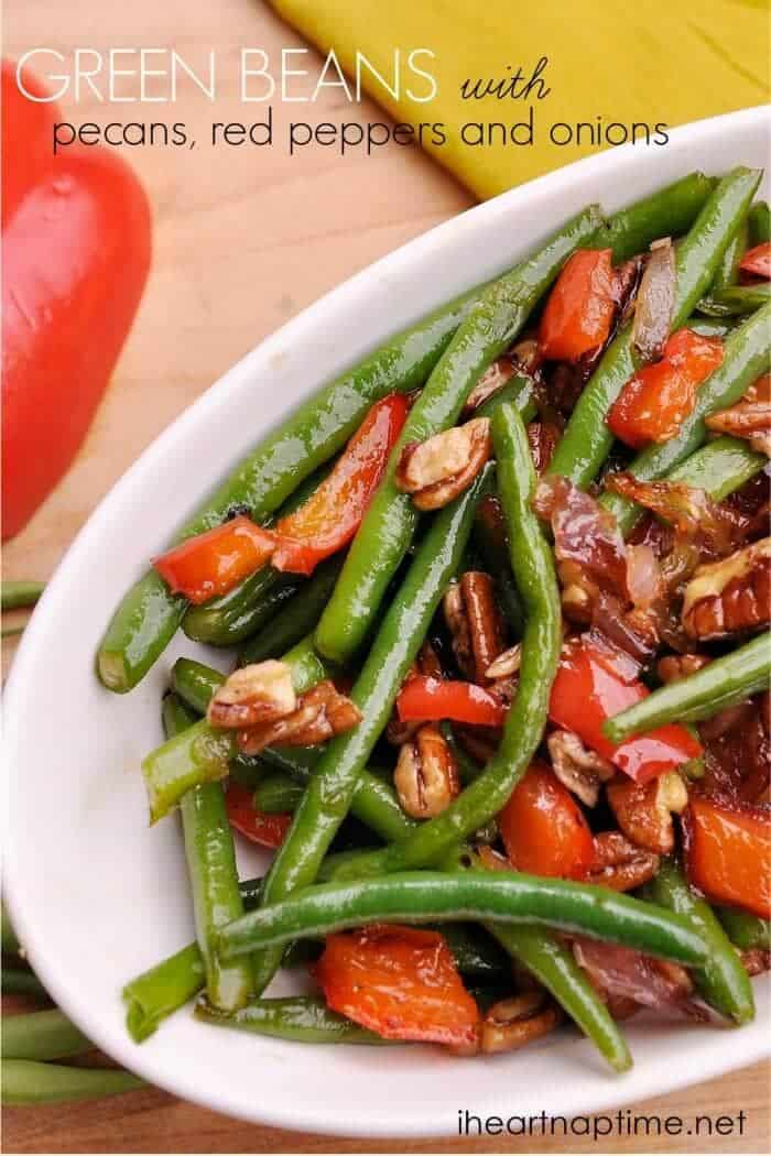 a close up of a bowl of green beans with red peppers and pecans