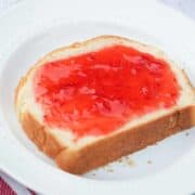 piece of homemade bread topped with fresh strawberry jam