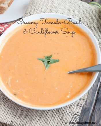 A bowl of tomato basil cauliflower soup with a spoon