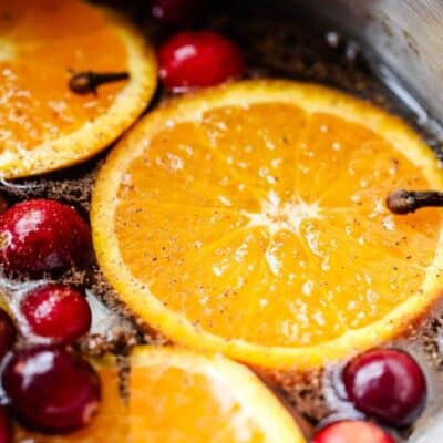 A close up of stovetop potpourri with fresh orange slices and cranberries