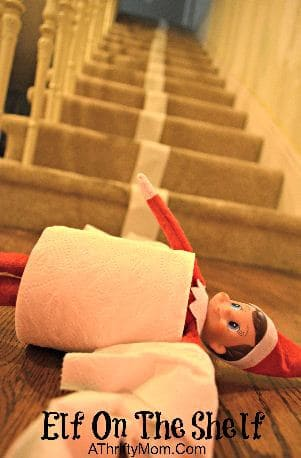 Elf rolling down the stairs in toilet paper