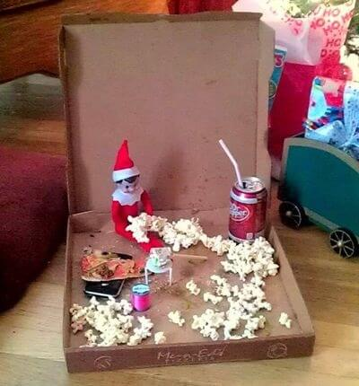 Elf eating popcorn in a pizza box