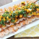 grilled shrimp skewers on a serving tray topped with mango salsa