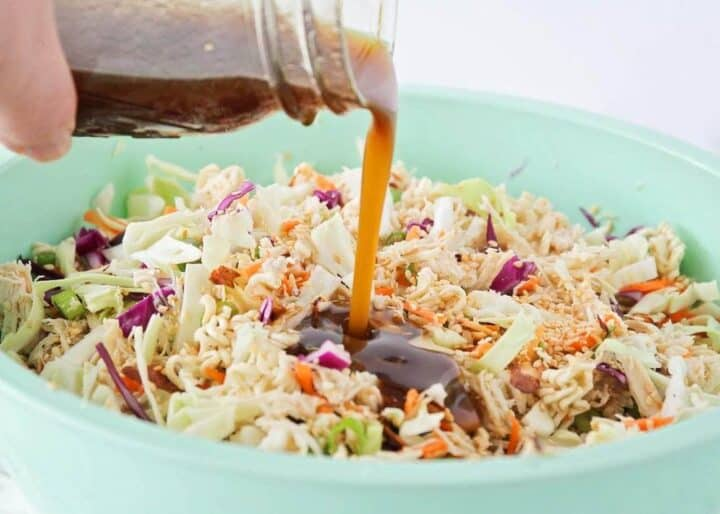 pouring dressing on top of ramen noodle salad