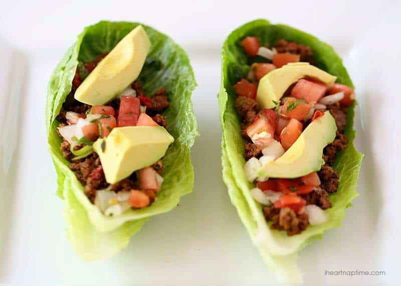 two taco lettuce wraps topped with pico de gallo and sliced avocado