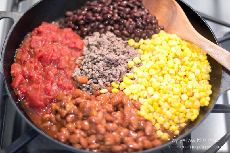 cooking chili ingredients on stove in cast iron skillet