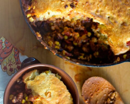 scooping chili cornbread skillet into a bowl