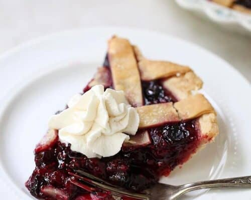 piece of razzleberry pie with whipped cream on a plate