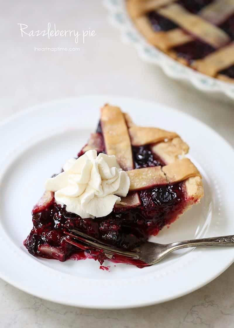piece of razzleberry pie on a white plate with whipped cream