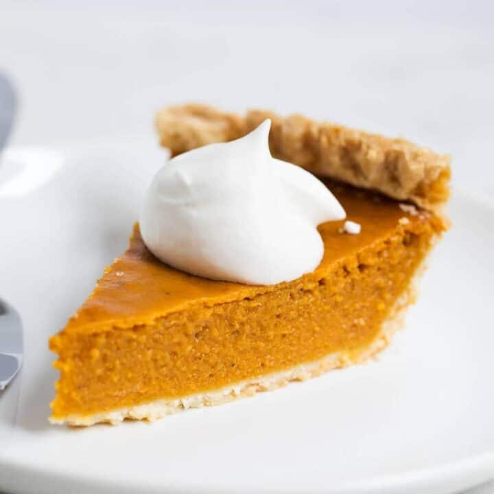 slice of pumpkin pie with homemade whipped cream on top