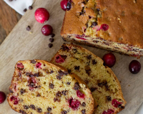 loaf of cranberry orange chocolate chip bread on wood table