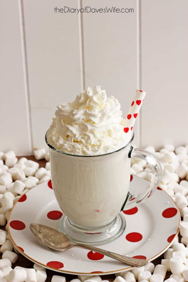 white chocolate cocoa in glass mug with whipped cream and straw