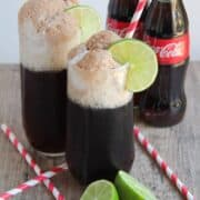coke float in a glass cup with a lime wedge and straw