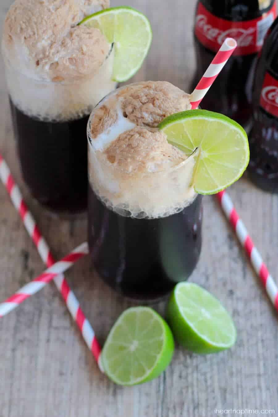 A close up of a coke float with a lime wedge and striped straw