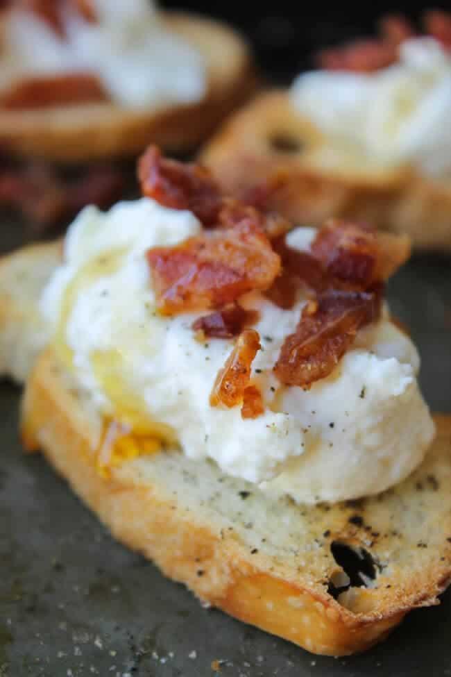 A close up of bacon ricotta crostini