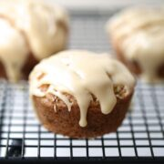 A close up of a maple glazed snickerdoodle muffin on cooling rack
