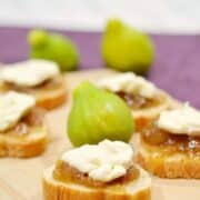 fig and brie bites sitting on wooden board