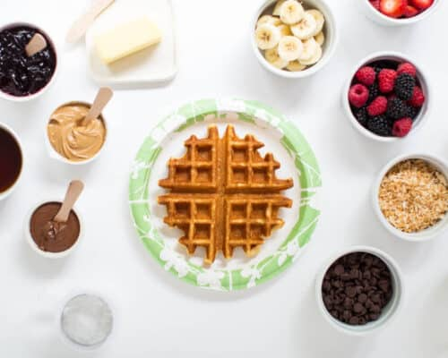 waffle on a paper plate with toppings on the counter