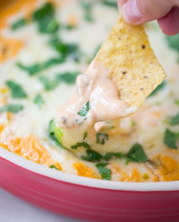 dipping a chip into chicken enchilada dip