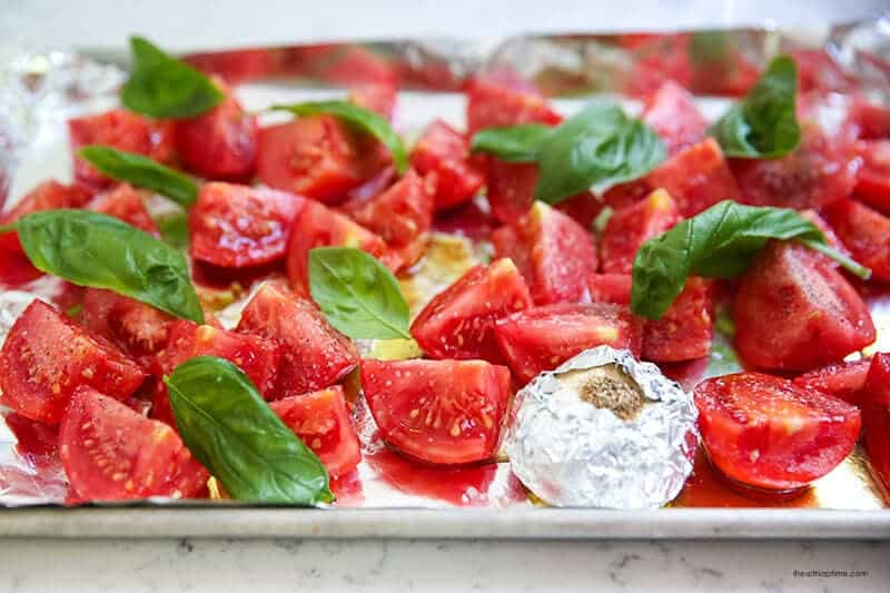 tomatoes and fresh basil on a baking sheet with olive oil, salt and pepper on top