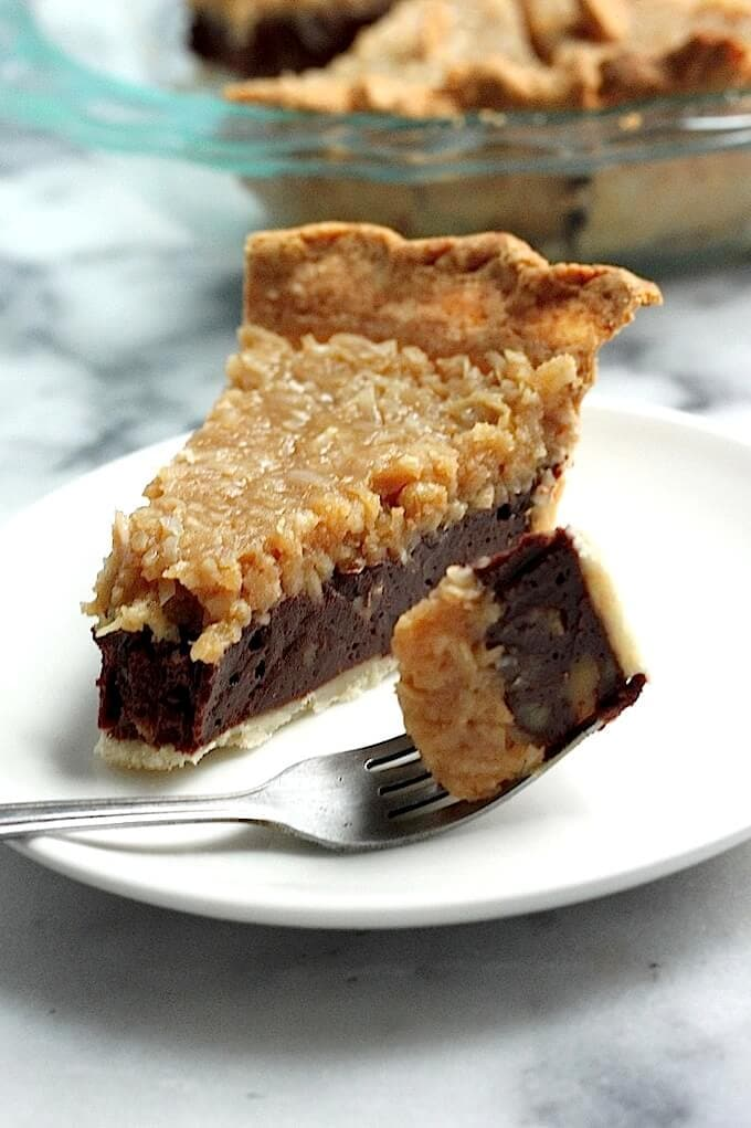 slice of chocolate coconut pecan pie on a plate with a fork