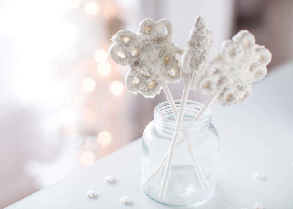 snowflake pretzels on a stick in a jar