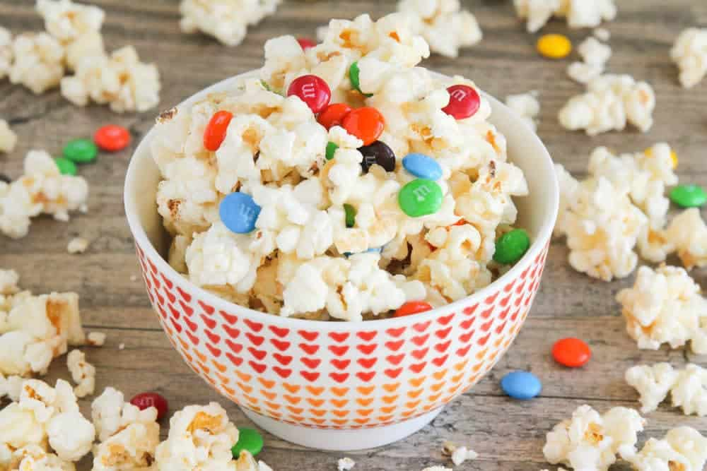 Delicious Caramel Corn - this recipe is super-easy and delicious, and the chocolate candies are the perfect addition. Perfect for parties (unless you don't feel like sharing!).