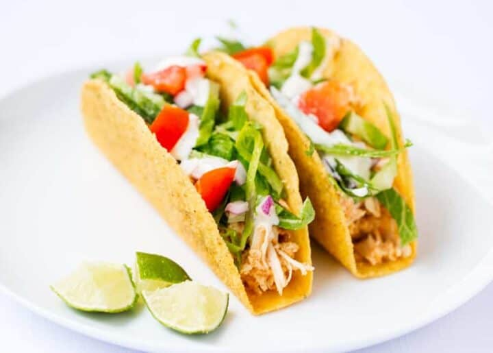 ranch chicken tacos on white plate with lime wedges