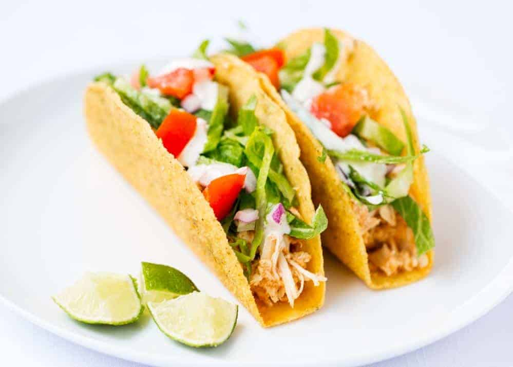 shredded chicken tacos on white plate with lime wedges