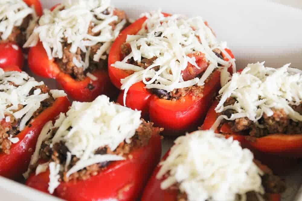 quinoa stuffed bell peppers with shredded cheese on top