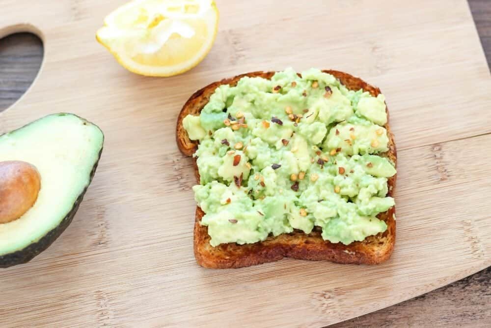 spread the mashed avocado onto the piece of toasted whole grain bread ...